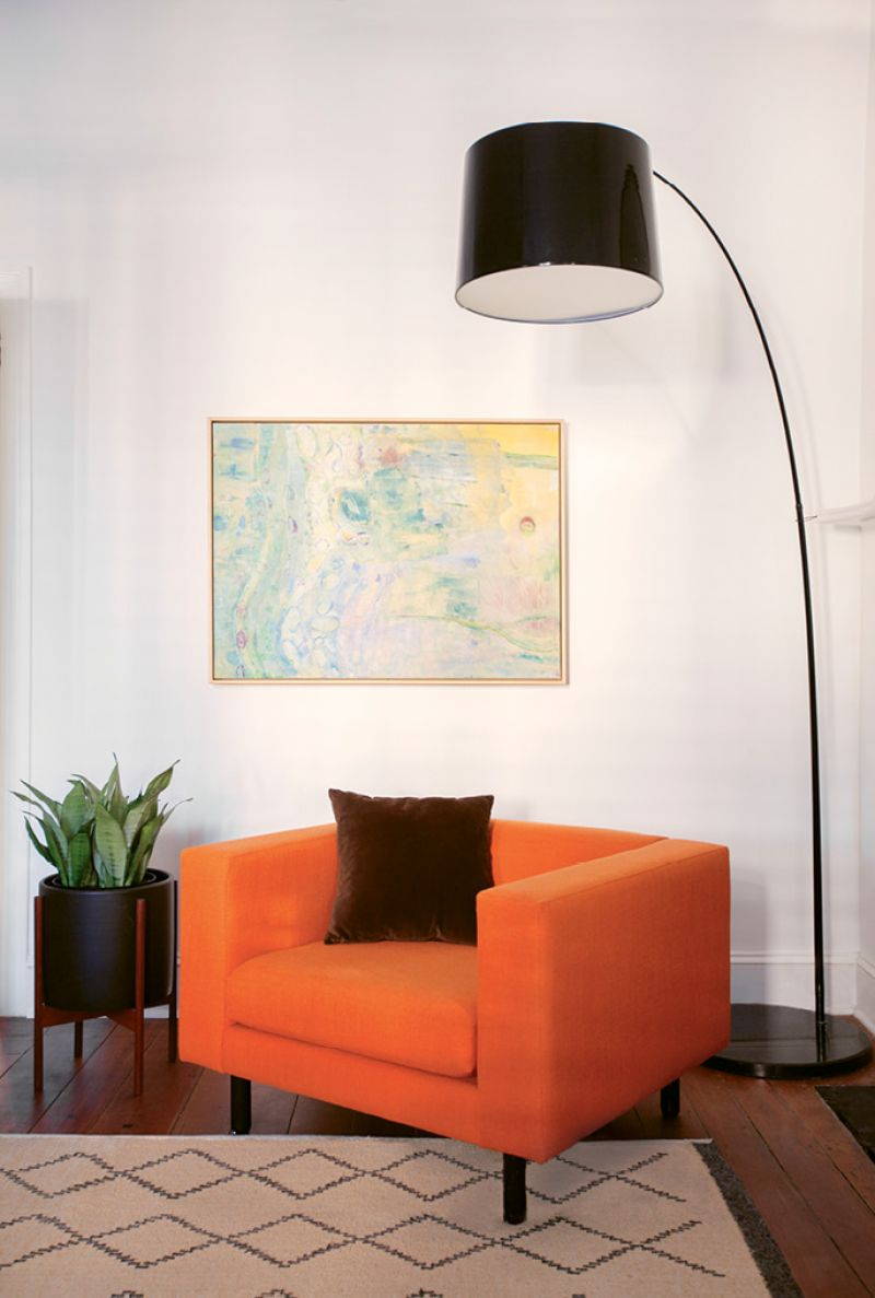 """The vibrant orange of the Blu Dot """"Mono Lounge Chair,"""" placed before a painting by local artist Diane Jerue"""