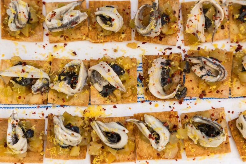 White Anchovy, Green Tomato Agrodolce with squid ink aioli, lavash, and cured egg yolk, prepared by Michael Holler of Indaco