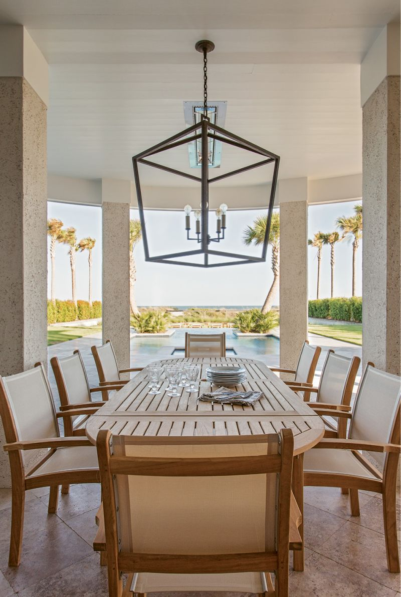 The View from Here: A teak dining table and Currey and Company light fixture set the stage for elegant outdoor dining.