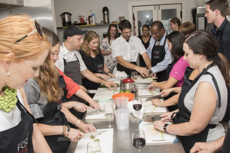 Chef Alessandro Pepe helps the class chop the scallions.