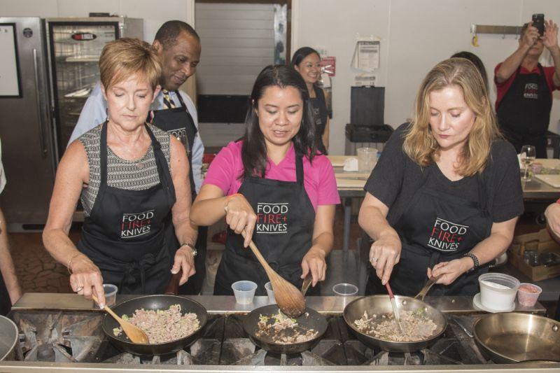 Gerri Greenwood, Vanessa White, and Amanda Samson saute ground pork for the lettuce wraps.