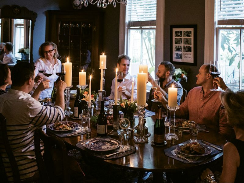 Friends raise glasses of wine around the candlelit table while Wagner gives a toast.